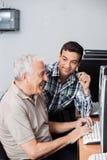 Teacher Assisting Senior Man In Using Computer Lab Stock Image