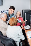 Teacher Assisting Senior People In Using Computer At Classroom Stock Photo