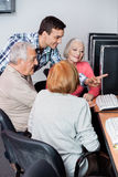 Teacher Assisting Senior Students In Using Computer At Classroom Stock Image