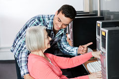 Teacher Assisting Senior Woman In Using Computer Stock Image