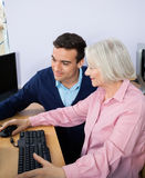 Teacher Assisting Senior Woman In Using Computer. Young male teacher assisting senior women in using computer at classroom Royalty Free Stock Photography