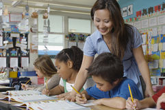 Teacher Assisting Student. Happy teacher assisting student in the classroom Stock Photos