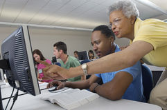Teacher Assisting Student In Computer Class. Senior teacher assisting male student during computer class with classmates in the background Royalty Free Stock Photos