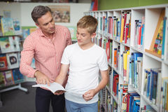 Teacher assisting student in reading book in library. At school Royalty Free Stock Photography