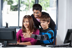Teacher Assisting Teenage Students In Computer Lab. Young African American female teacher assisting teenage school students in computer lab Royalty Free Stock Photo