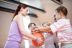 PE teacher holding basketball ball while standing near children