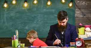 Teacher with beard, father drawing while little son hang out near, in classroom, chalkboard on background. Child and royalty free stock image