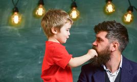 Teacher with beard, father and little son having fun in classroom, chalkboard on background. Dad with beard spend time. With son. Child cheerful play with beard royalty free stock photos