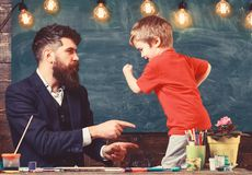 Teacher with beard, father and little son having fun in classroom, chalkboard on background. Fatherhood concept. Child royalty free stock photography
