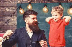 Teacher with beard, father and little son having fun in classroom, chalkboard on background. Fatherhood concept royalty free stock photos