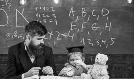 Teacher with beard, father teaches little son in classroom, chalkboard on background. Boy, child on calm face holds. Alarm clock while teacher talk to kid royalty free stock images