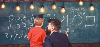 Teacher with beard, father teaches little son in classroom, chalkboard on background. Boy, child in graduate cap stock image