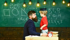 Teacher with beard, father teaches little son in classroom, chalkboard on background. Boy, child in graduate cap play. With dad, having fun and relaxing during stock photos