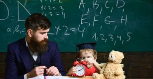 Teacher with beard, father teaches little son in classroom, chalkboard on background. Individual lesson concept. Boy. Child on calm face holds alarm clock royalty free stock photos
