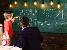 Teacher with beard, father teaches little son in classroom, chalkboard on background. Prodigy child concept. Boy, child. In graduate cap discussing scribbles on stock photos