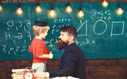 Teacher with beard, father teaches little son in classroom, chalkboard on background. School break concept. Boy, child royalty free stock image