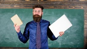 Teacher bearded hipster holds book and laptop. Choose right teaching method. Modern instead outdated. Teacher choosing stock photo