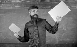 Teacher bearded hipster holds book and laptop. What would you prefer. Teacher choosing modern teaching approach. Paper. Book against laptop. Digital against royalty free stock photos