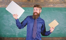 Teacher bearded hipster holds book and laptop. What would you prefer. Teacher choosing modern teaching approach. Paper. Book against laptop. Digital against royalty free stock photo