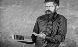 Teacher bearded man confused work with modern laptop chalkboard background. Hipster teacher confused expression holds royalty free stock photography