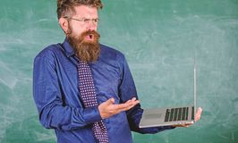 Teacher bearded man confused work with modern laptop chalkboard background. Hipster teacher confused expression holds royalty free stock photo
