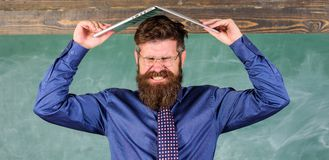 Teacher bearded man with modern laptop chalkboard background. Can not get used to teachers lifestyle. School blows his. Mind. Hipster teacher aggressive with royalty free stock images