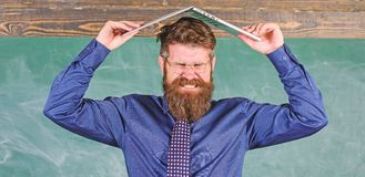 Teacher bearded man with modern laptop chalkboard background. Can not get used to teachers lifestyle. School blows his. Mind. Hipster teacher aggressive with stock image