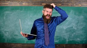 Teacher bearded man with modern laptop chalkboard background. Hipster teacher aggressive with laptop goes mad about. Modern technology. Technology blows his royalty free stock images