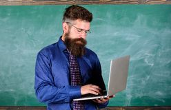 Teacher bearded man with modern laptop chalkboard background. Online education. Modern technology education. Hipster. Teacher wear eyeglasses and necktie holds stock photography
