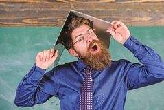 Teacher bearded man with modern laptop chalkboard background. School blows his mind. Hipster teacher aggressive with. Laptop as roof goes mad about teaching stock image