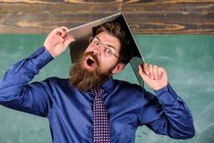 Teacher bearded man with modern laptop chalkboard background. School blows his mind. Hipster teacher aggressive with. Laptop as roof goes mad about teaching stock photos