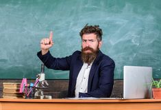 Teacher bearded man tell interesting story.Teacher interesting interlocutor as best friend. Teacher charismatic hipster. Sit table classroom chalkboard stock image