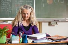 Teacher behind her desk Stock Photos