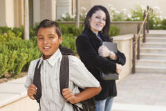 Teacher Behind Hispanic Boy Student with Backpack on School Campus. Happy Hispanic Boy with Backpack on School Campus and Teacher Behind Royalty Free Stock Photography