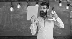 Teacher of biology in eyeglasses holds book and microscope. Man with beard on calm face in classroom. Scientist holds. Book and microscope, chalkboard on stock images