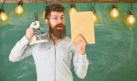 Teacher of biology in eyeglasses holds book and microscope. Man with beard on surprised face in classroom. Biology. Concept. Scientist holds book and microscope royalty free stock photo