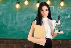 Teacher of biology holds book and microscope. Lady in formal wear on calm face in classroom. Biology concept. Lady. Scientist holds book and microscope royalty free stock image