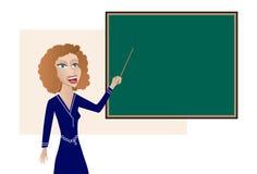 Teacher at the Blackboard. Female teacher gesturing towards a blackboard (chalkboard) which features copyspace Royalty Free Stock Image