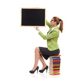 Teacher with blackboard. Female teacher sitting on colorful stack of books and holding a blackboard. Full length studio shot isolated on white Stock Images