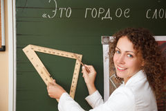 Teacher at blackboard with ruler and pencil Stock Image