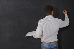 Teacher at the blackboard. Teacher writing on a blackboard with a book in his hand Stock Image