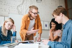 Teacher with blond hair and beard leaning on table and emotionally explaining something to students. Group of upset stock photography