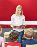 Teacher with book in elementary Stock Photos