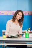 Teacher With Book Sitting At Desk In Classroom Stock Photo