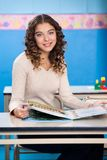 Teacher With Book Sitting At Desk In Preschool royalty free stock photo