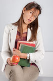 Teacher with books and apple. Teacher with book and apple seating on desk Stock Photos