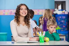 Teacher With Bored Boy Sitting At Desk In. Portrait of beautiful teacher with bored boy sitting at desk in classroom Royalty Free Stock Photo