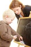 Teacher and boy. Boy drawing on a blackboard, teacher watching Royalty Free Stock Photo