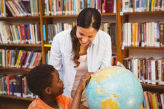 Teacher and boy looking at globe in library Stock Photo