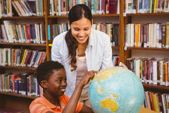 Teacher and boy looking at globe in library Royalty Free Stock Photo